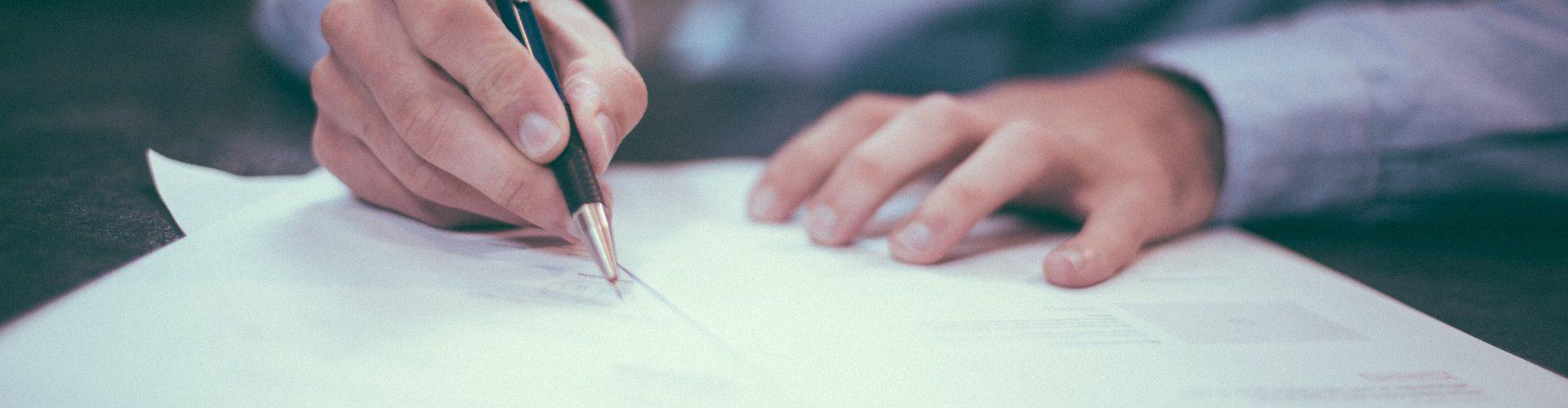 Bild zeigt einen Vertrag, der unterschrieben wird